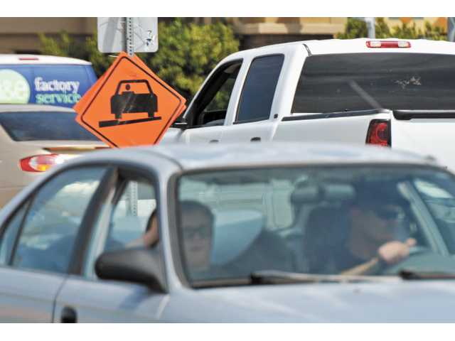 Motorists pass a sign warning of uneven pavement on Bouquet Canyon Road near Newhall Ranch Road in Valencia on Wednesday.