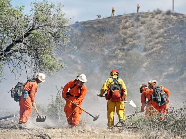 A hand crew clears brush near a charred hillside blackened by a brush fire in Bouquet Canyon on Monday. The fire was whipped by near-hurricane-force winds. Signal photo by Jonathan Pobre