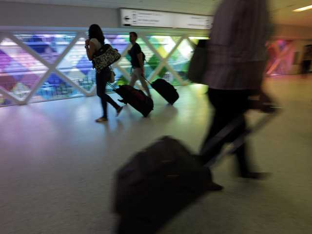 In this Sept. 2012 photo, passengers travel through an airport in Miami. Researchers say consumer complaints to the Department of Transportation surged by one-fifth last year.