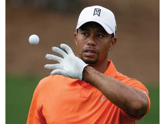 Tiger Woods catches a ball while hitting on the driving range during a practice round for the Masters Tournament on Monday in Augusta, Ga.