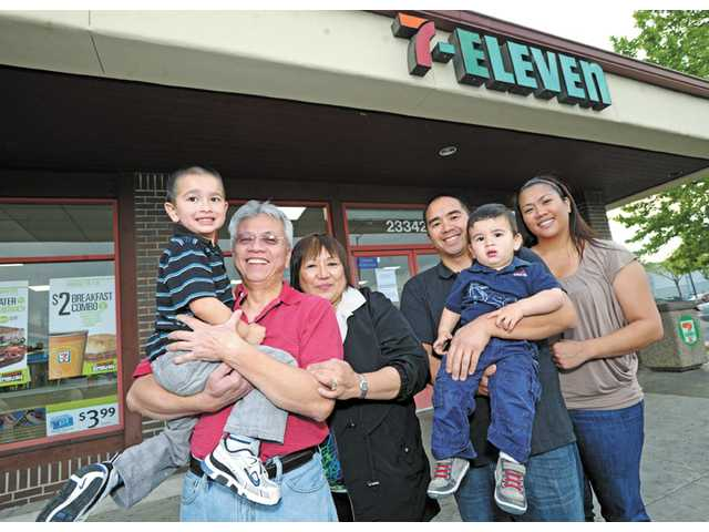 Members of the Manalastas family pose in front of their 7-Eleven store at 23342 Valencia Blvd. in Valencia. From left, Danny Manalastas carries his grandson Jacob, 4, and is accompanied by wife Marylou, son Ron, grandson Joshua, 1, and daughter Aimee. The 7-Eleven company decided to close the Valencia store after 27 years of operation. But the company is offering Manalastas the opportunity to open a store anywhere in the world and will cover his franchise fee.