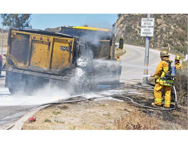 Firefighters douse the smoldering rear section of a dump truck on the northbound Highway 14 on-ramp at Newhall Avenue on Tuesday. Signal photo by Jonathan Pobre