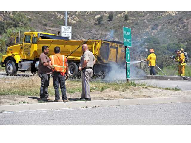 Trucking company workers speak with a California Highway Patrol officer as firefighters douse the smoldering section of a dump truck on the Newhall Avenue on-ramp to the northbound Highway 14 on Tuesday. Signal photo by Jonathan Pobre