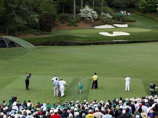 In this April 8, 2010, file photo, Tiger Woods tees off at the 12th hole during the first round of the Masters golf tournament in Augusta, Ga. The shortest hole at Augusta National is found in the heart of Amen Corner, and it's 155 yards of sheer hell.