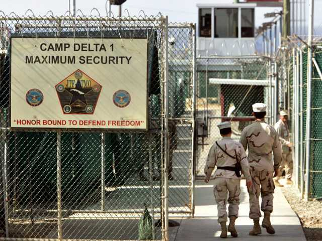 In this file photo made June 27, 2006, reviewed by a U.S. Department of Defense official, U.S. military guards walk within Camp Delta military-run prison, at theGuantanamoBay U.S. Naval Base, Cuba.