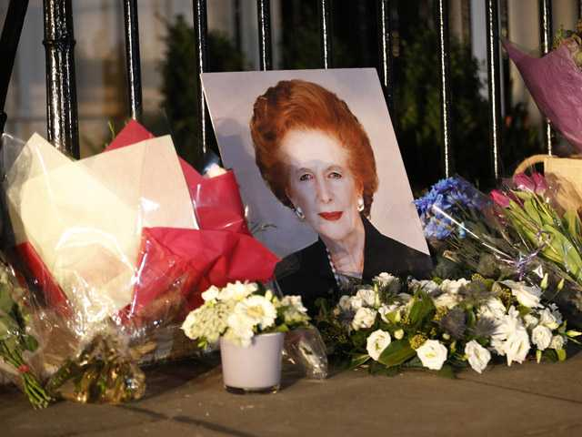 "Flowers placed by well-wishers surround a portrait of former British Prime Minister Margaret Thatcher outside her home in Belgravia, London, Monday, April 8, 2013. Margaret Thatcher, the combative ""Iron Lady"" who infuriated European allies, found a fellow believer in Ronald Reagan and transformed her country by a ruthless dedication to free markets in 11 bruising years as prime minister, died Monday. She was 87 years old. (AP Photo/Sang Tan)"