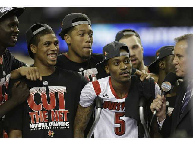 Louisville players and Louisville guard Kevin Ware (5) celebrate their team's win over Michigan 82-76 in the NCAA college basketball championship on Tuesday in Atlanta.