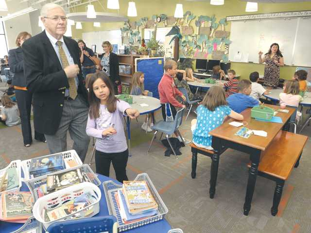 L.A. County Supervisor Michael D. Antonovich, left, is led through the thrid-grade classrom at SCVi charter school in Castaic by third-grader Emily Barragan today. Signal photo by Dan Watson