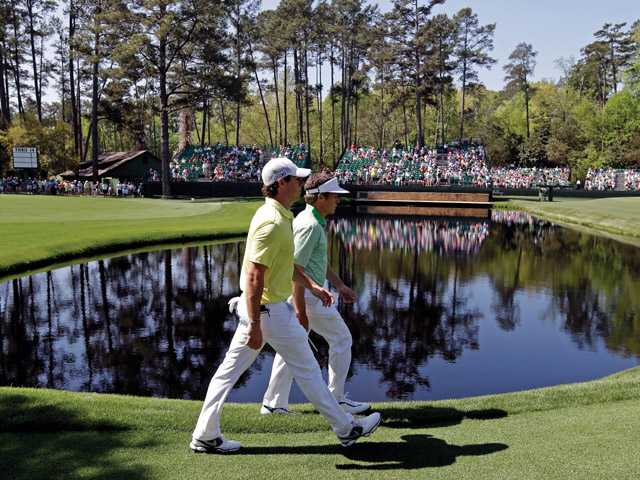 Rory McIlroy walks with amateur Michael Weaver to the 15th green during a practice round for the Masters golf tournament Wednesday in Augusta, Ga.