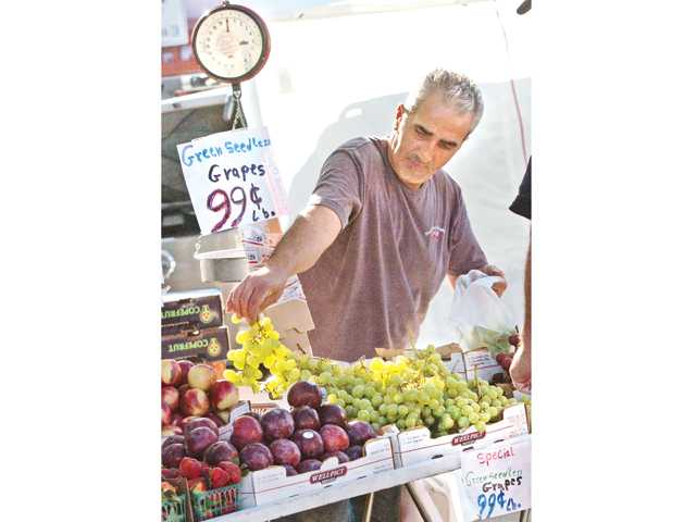 Sami Yordi of Daily Produce bags a bunch of grapes for a customer at the Farmer's Market held Thursdays on Main Street in Newhall. Signal photo by Dan Watson