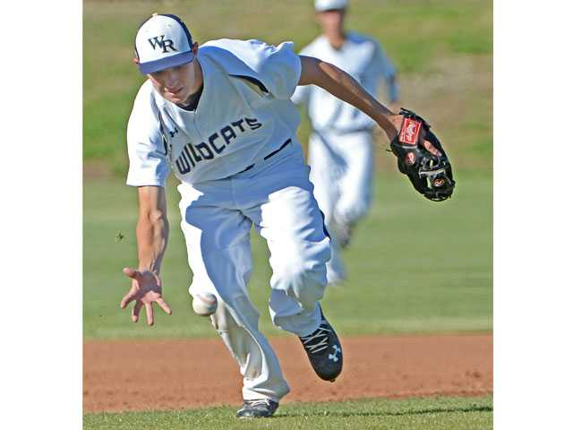 West Ranch third baseman J.D. Krauskopf scoops up a grounder with his bare hand at Canyon High School on Wednesday.
