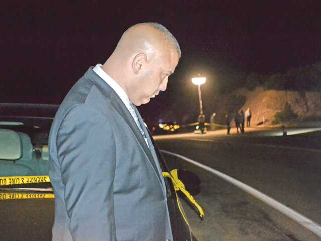 Homcide Detective Lt. Eddie Hernandez walks past the scene of a body discovered about 20 feet from San Francisquito Canyon Road in Saugus on Wednesday. Signal photo by Kirsten Quinn