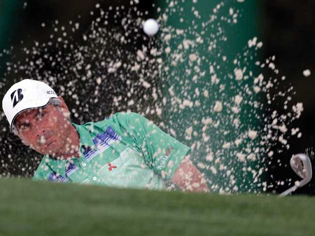 Fred Couples hits out of a bunker on the 18th green during the first round of the Masters golf tournament Thursday in Augusta, Ga.