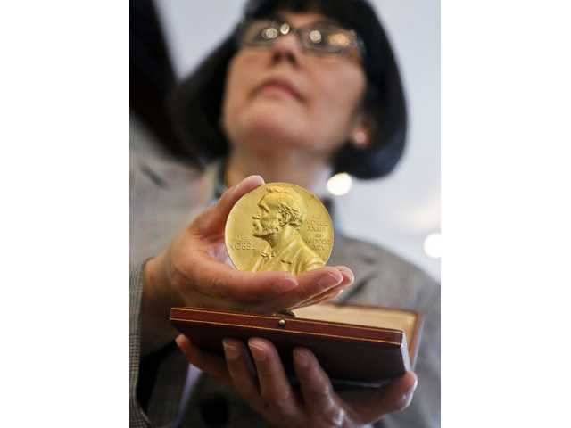 Sandra Palomino, director of historical manuscripts at Heritage Auctions, holds the 1962 Nobel Prize for Physiology or Medicine awarded to Dr. Francis Harry Compton Crick.