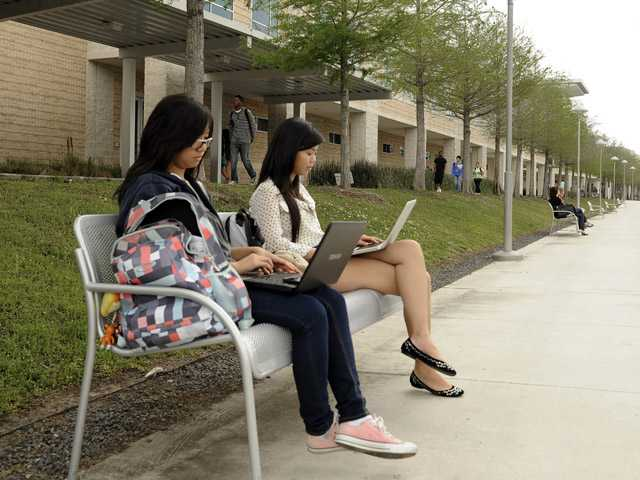 Students Nai Xin Zheng, left, and Tu Cao work on school projects the day after at least 14 people were wounded by a knife-wielding student, Dylan Quick, at the Lone Star Community College in Cypress, Texas.