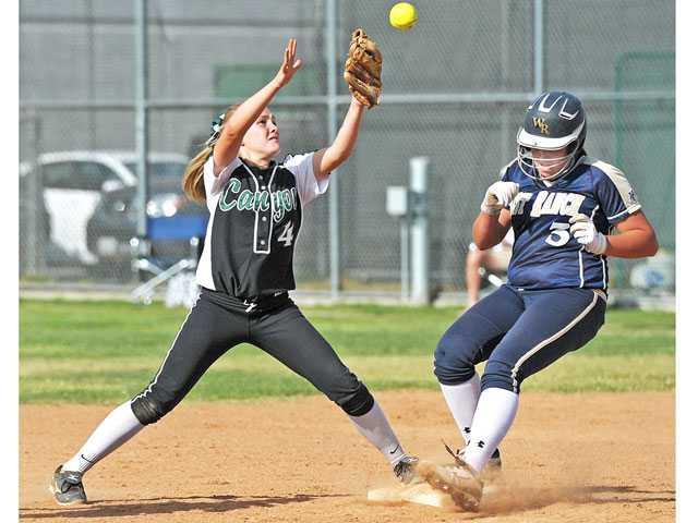 Canyon second baseman Amanda Doyle (4) can't make the catch as West Ranch's Keeley Walsh (3) beats the tag to second base in the fifth inning on Thursday at Canyon High.