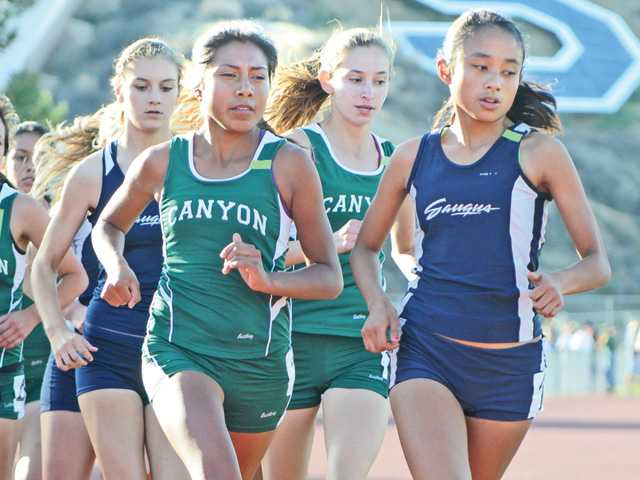 Samantha Ortega, right, of Saugus leads the pack during the 3200 meter race against Canyon High at Saugus on Thursday.