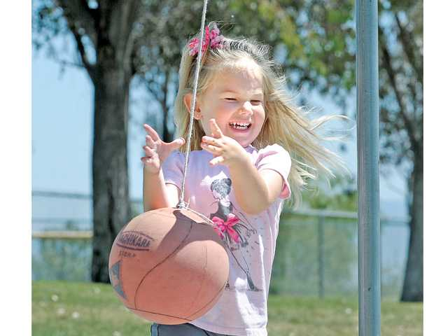 Callie Scheidt, 3, plays tether ball at Richard H. Rioux Memorial Park in Stevenson Ranch on Friday as temperatures rose to 80 degrees in the Santa Clarita Valley. Signal photo by Dan Watson