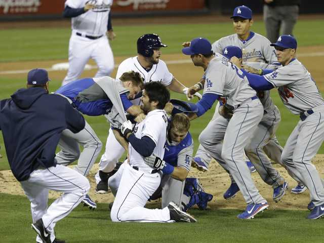 San Diego Padres' Carlos Quentin and teammates battle the Los Angeles Dodgers after Quentin was hit by a pitch thrown by Dodgers pitcher Zack Greinke in San Diego on Thursday..