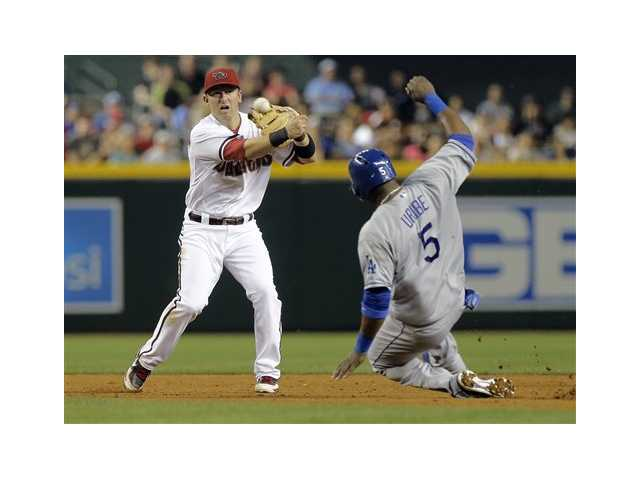 Los Angeles Dodgers' Juan Uribe is forced out as Arizona Diamondbacks' Cliff Pennington turns a double play.