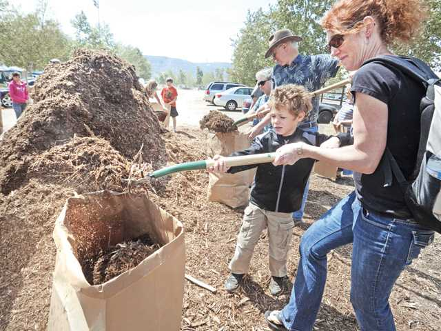 Marcus Roberts, 6, center, and Karen Roberts of Castaic fill a bag with mulch at the city of Santa Clarita Earth Arbor Day event held at Central Park in Saugus Saturday.