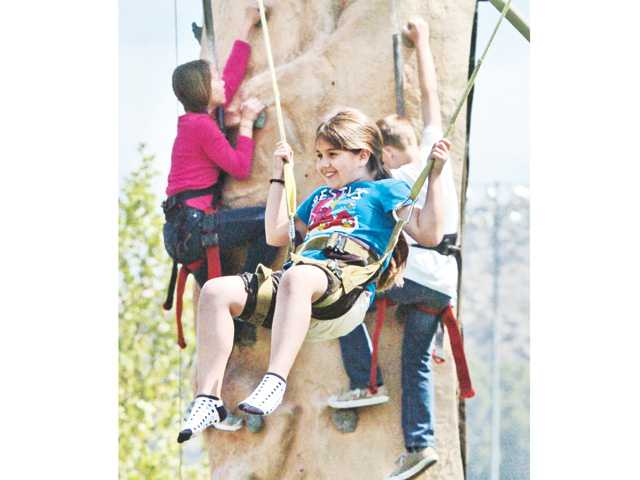 Azul Villatoro, 9, of Saugus bounces on the Monkey Jump as climbers behind her creep up the climbing wall at the city of Santa Clarita Earth Arbor Day event held at Central Park in Saugus Saturday.