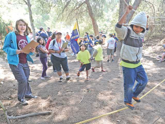 Cub scout Rubin Montano, 6, is cheered on as he slides along a rope bridge during the Cup Scout Cup event held at the William S. Hart Park campgrounds on Saturday.
