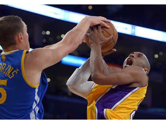 Golden State Warriors forward Andris Biedrins, of Latvia,, left, blocks the shot of Los Angeles Lakers guard Kobe Bryant on Friday in Los Angeles.