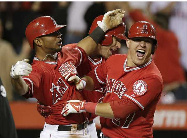 Los Angeles Angel Mike Trout, right, celebrates after scoring the winning run on a Albert Pujols hit on Saturday in Anaheim.