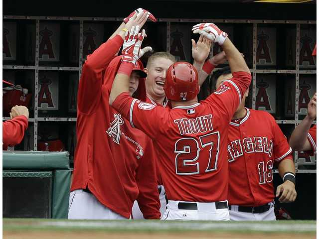Los Angeles Angels congratulate teammate Mike Trout (27) after his home run against the Houston Astros in Anaheim on Sunday.