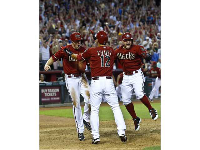 Arizona Diamondbacks' A.J. Pollock, left, celebrates his game-winning run against the Los Angeles Dodgers.