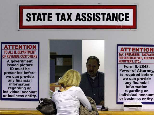 In this Monday, April 16, 2012 file photo, an Illinois Department of Revenue employee offers assistance to income tax payers at the Illinois Department of Revenue, in Springfield, Ill.