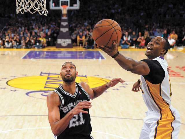 Los Angeles Lakers center Dwight Howard, right, shoots as San Antonio Spurs forward Tim Duncan defends Sunday in Los Angeles.