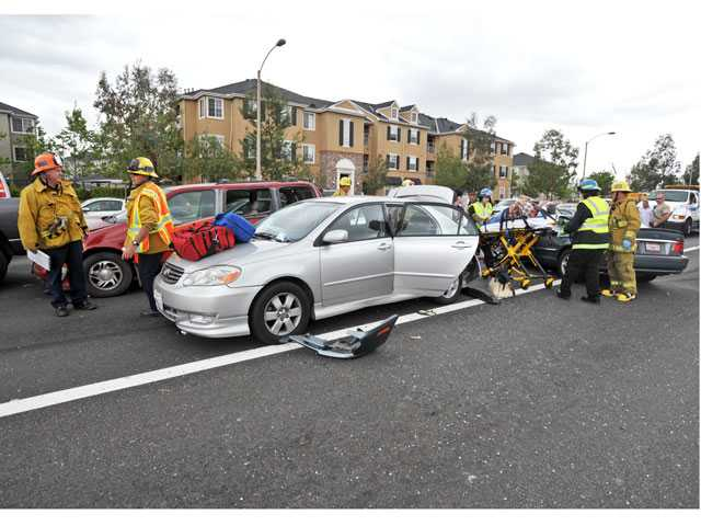 Emergency medical technicians take a motorist, right, on a gurney to an ambulance at the scene of a six-vehicle collision on eastbound Newhall Ranch Road near McBean Parkway in Valencia on Monday. Signal photo by Jonathan Pobre