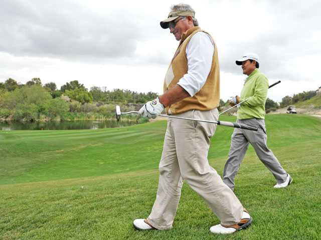 Marty Bailey, left, and Fred Choi make their way to the fourth green in the Sheriff's Shootout golf tournament Monday, which benefits the Sheriff's Youth Foundation of Los Angeles County. Signal photo by Jonathan Pobre
