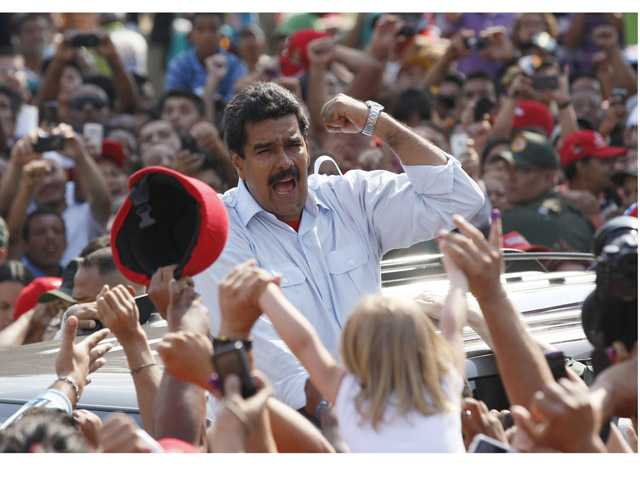 Venezuela's interim President Nicolas Maduro gestures to supporters as he leaves a polling station after voting in the presidential election in Caracas, Venezuela, Sunday, April 14.