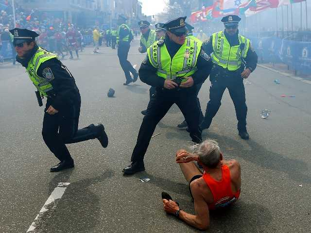 Police officers react to a second explosion at the finish line of the Boston Marathon in Boston, Monday.