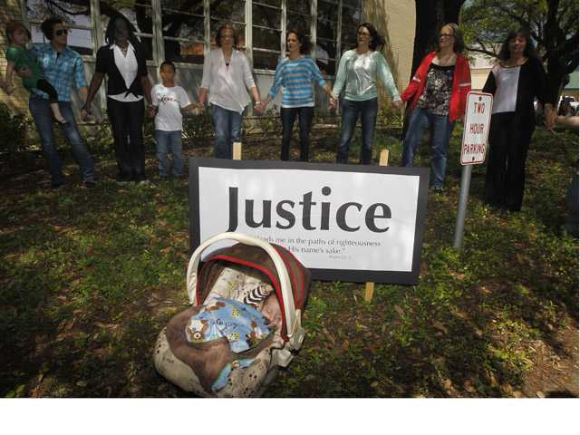 Angel Diaz, 3 months, daughter of Lorena Martinez, not pictured, rests as other pray during a prayer walk around the Kaufman County Courthouse in Kaufman, Texas on April 14.