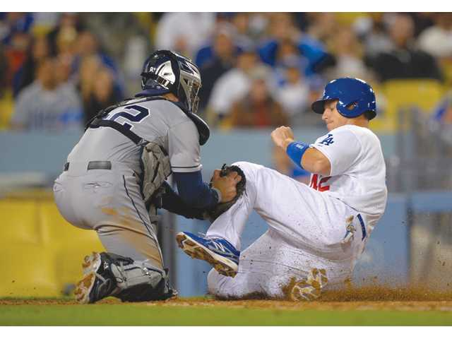 Los Angeles Dodger A.J. Ellis, right, is tagged out at home by San Diego Padres catcher John Baker on Monday in Los Angeles.