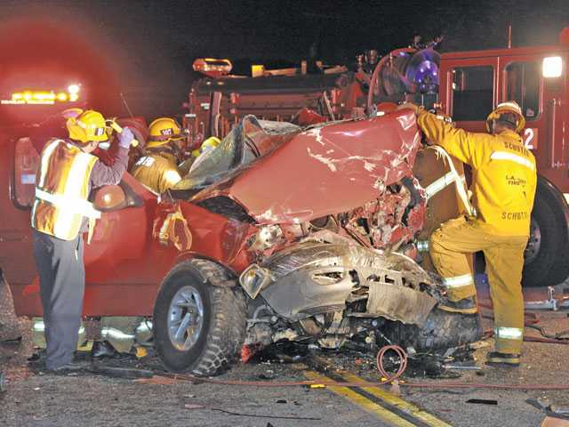 Firefighters work on a truck whose driver was killed during a head-on collision on Sierra Highway in January.