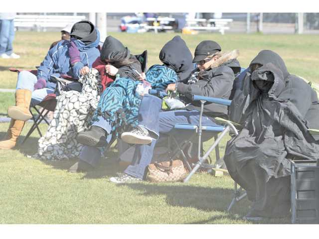 High winds kick up dust in the faces of spectators huddled under heavy coats and blanckets at the Hart High School vs. Golden Valley High School girls softball game held at Golden Valley High School on Tuesday afternoon in Santa Clarita.  Hart High won the game 10-0.