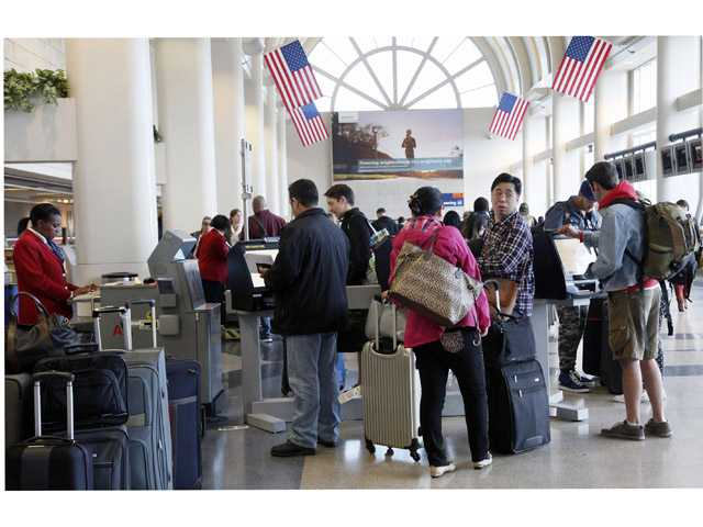Passengers at the American Airlines counter wait for checking in to their flights at Los Angeles International Airport on Tuesday.