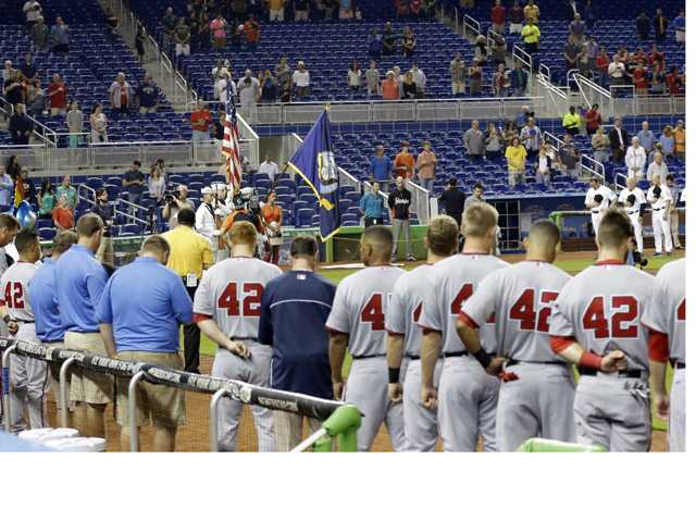 Baseball players and fans stand during a moment of silence for the victims of explosions at the Boston Marathon, before the start of a baseball game between the Miami Marlins and the Washington Nationals, Monday in Miami.