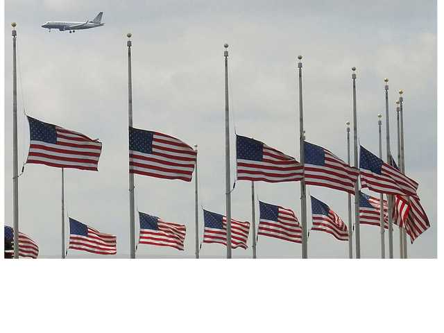 A jetliner flies over flags flying at half-staff at the Washington Monument in Washington Tuesday after President Obama ordered flags to be lowered on federal building to honor the loss of life from the explosions at the Boston Marathon.