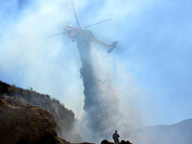 A helicopter drops water on the flames and a firefighter labors below during a 4-acre brush fire in Agua Dulce today. No structures were threatened. Photo by Rick McClure