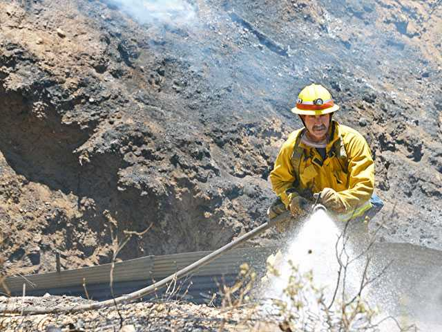 A firefighter from county Station 107 helps control a 4-acre brush fire along the Highway 14 freeway late Wednesday morning. No structures were threatened, and quick action by county and Anteles National Forest firefighters had the flames largely doused shortly after noon. Photo by Rick McClure