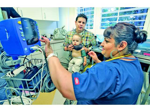 Father Julian Andrade holds his son ten-month-old Matias as medical assistant Annalise D'Souza checks the boy's vital signs in an examination room at Children's Hospital Los Angeles Valencia Clinic in May 2012.
