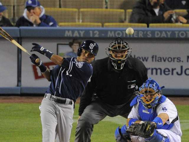 San Diego Padres' Alexi Amarista, left, hits an RBI single as Los Angeles Dodgers catcher A.J. Ellis catches Tuesday in Los Angeles.