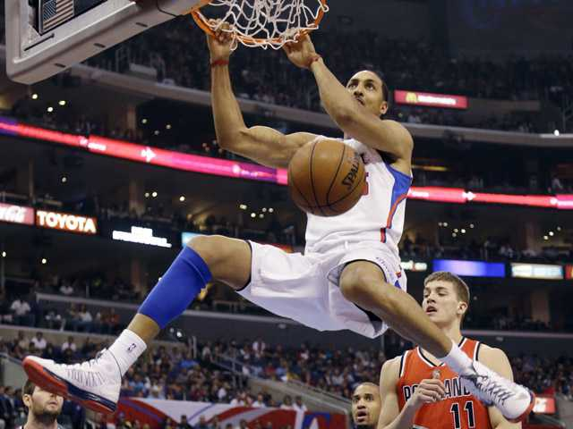 Los Angeles Clippers center Ryan Hollins (15) dunks over Portland Trail Blazers center Meyers Leonard (11) in Los Angeles on Tuesday.