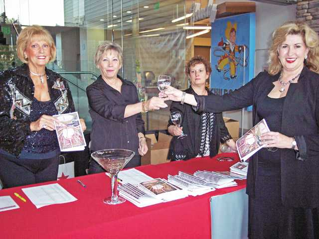 Left to right, Judy Penman, Cheryl Gray and Brenda Kay toast Marlee Lauffer, vice chairwoman of the WiSH Education Foundation. Lauffer also served as co-host of the wine tasting event held Saturday at the Newhall Library. Photo by Michele Buttleman